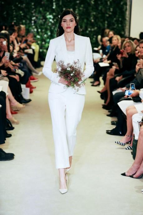 C'est Carolina Herrera qui ouvre le bal avec ce magnifique smoking de mariée tout de blanc vêtu. Très bien coupé, sobre et chic, le petit plus de cet ensemble est le pantalon qui s'arrête juste au-dessus de la cheville pour la dévoiler sensuellement. Avec cela on mise sur des escarpins à bout pointu et un bouquet coloré !  Carolina Herrera, Collection 2016, Jinni
