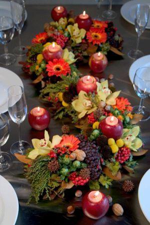 Ce serpent d'automne  habille la table de manière a crée une ambiance de forêt enchantée. On y retrouve la pomme en utilisée ici comme bougeoir , des radis , des choux de Bruxelles , des raisins...