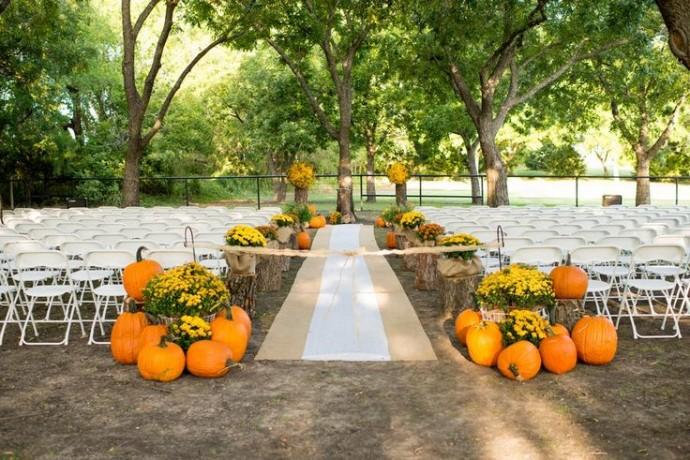 Voici un autre exemple d'une décoration d'extérieur avec des citrouilles. Pleine de pep's, elle ajoute une somptueuse touche d'orangé à cette jolie allée de mariage !