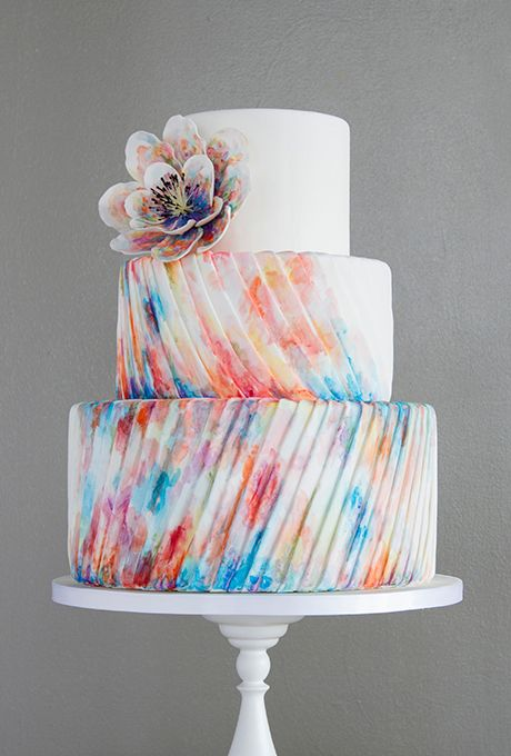Surprenant gâteau monté sur trois étages avec son nappage coloré et sa jolie rose au sommet.