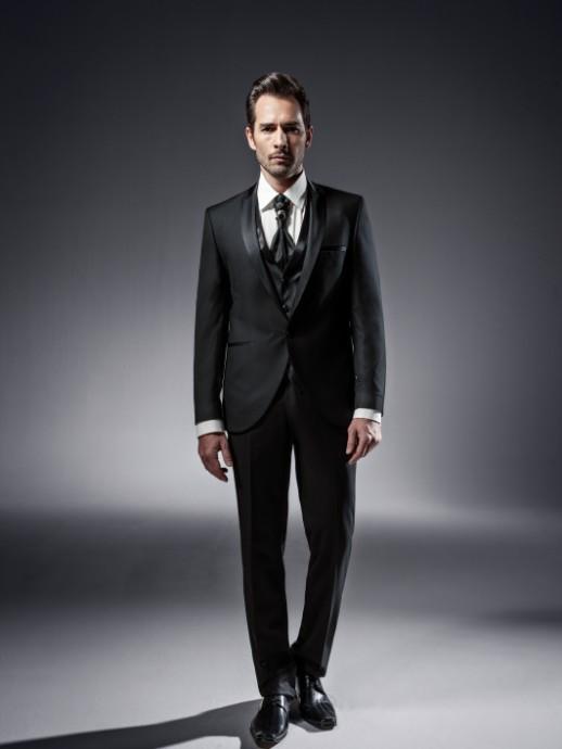 Un smoking quatre pièces noir et satiné pour un marié qui aime le sombre et l'élégance. Le col de chemise est classique et le gilet est accompagné d'une lavallière et de son bijou. Un costume signé Pronuptia.