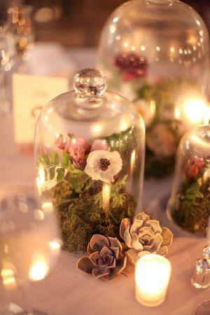 Entourée de multiples bougies, la cloche en verre peut renfermer de belles fleurs afin de faire un magnifique centre de table pour une décoration romantique.