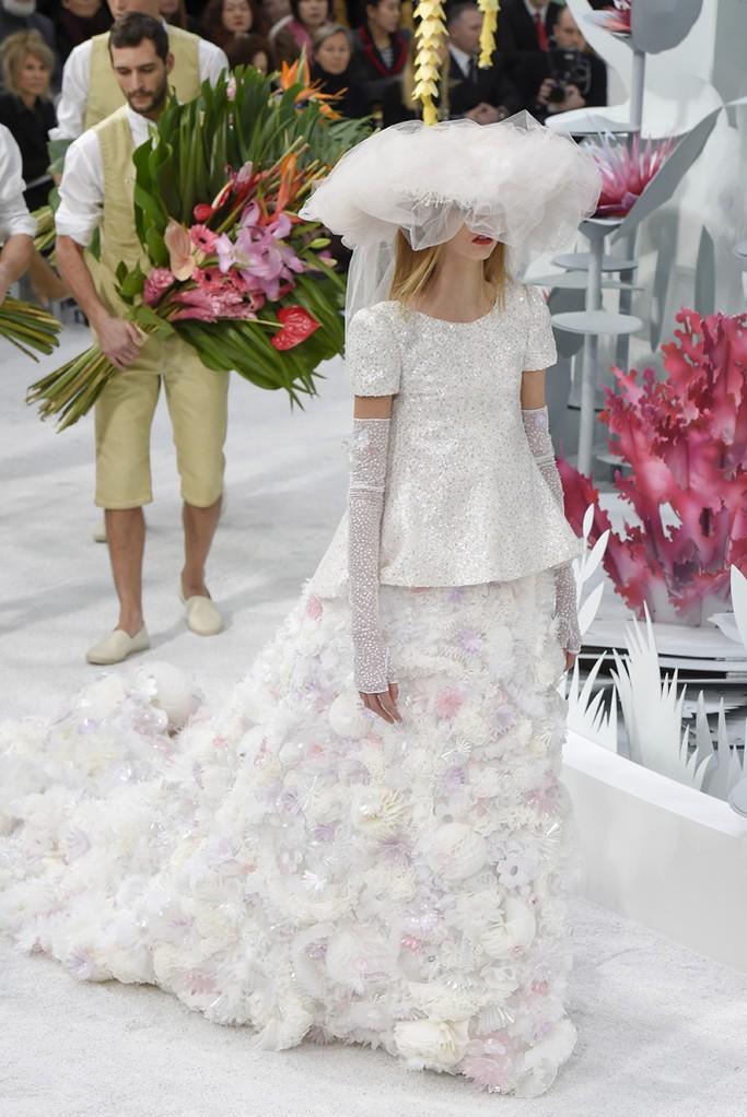 Impossible de sélectionner les plus belles robes de cette année sans mentionner la robe du défilé Chanel Haute-Couture, présentée lors de la collection printemps-été 2015. A la fois romantique et sophistiquée, Karl Lagerfeld a enlevé le traditionnel voile pour y mettre une capeline et un nuage de tulles. C'est dans un esprit floral qu'est présentée cette robe sublime.