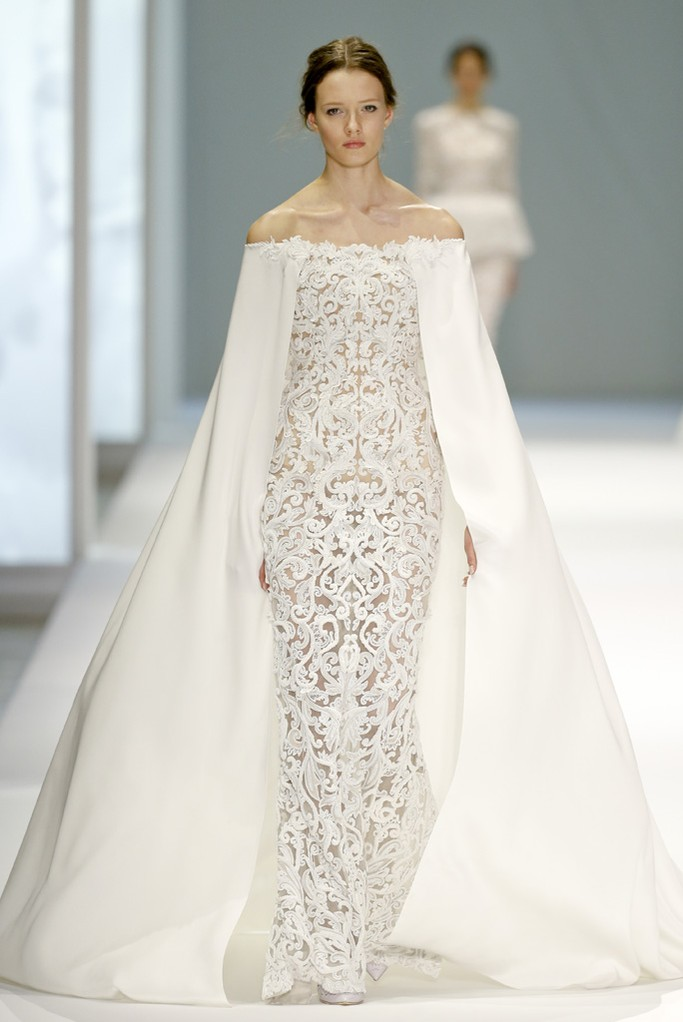 Ralph & Russo a dévoilé une belle perle lors de la présentation de sa collection printemps/été 2015. Cette robe en dentelle serrée, et sa large cape donne un contraste sublime à cette robe qu'on rêve d'épouser aussi !