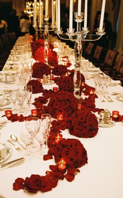 Vous voulez du rouge toute en élégance ? Optez pour une nappe blanche et un délicat chemin de roses rouges. Pour une ambiance encore plus chaleureuse, vous pouvez y rajouter quelques bougies !