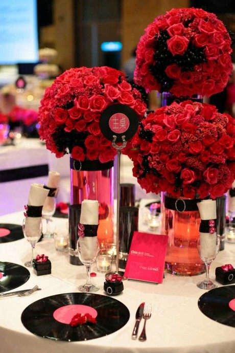 Pour une décoration, plus rock'n'roll. Vous pouvez associer roses rouges et vinyles sur une délicate nappe blanche.