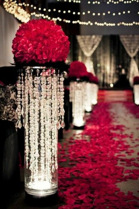 Pour une décoration tout en brillance, on opte pour des rideaux de perles, de la lumière tamisée, et des roses rouges.