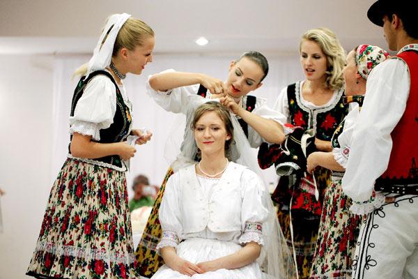 Des femmes habillées en tenues traditionnelles retire le voile de la marié