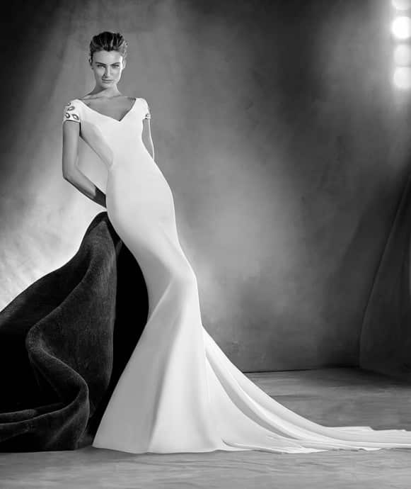 Very elegant mermaid-cut wedding dress with a spectacular V neckline and plunging back with elegant buttons. A model that flatters feminine curves, with gemstone details on the sleeves that give it a chic touch.
