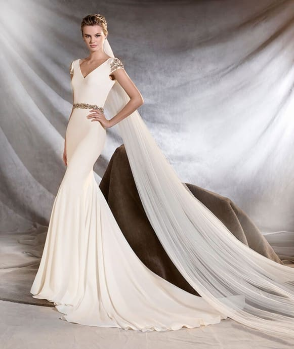 Exquisite crepe mermaid wedding dress, fitted to the hips, with a v-neck. A sublime creation that gives a bride a distinguished touch: beautiful gemstone-encrusted sleeves and waist that sculpts the figure.