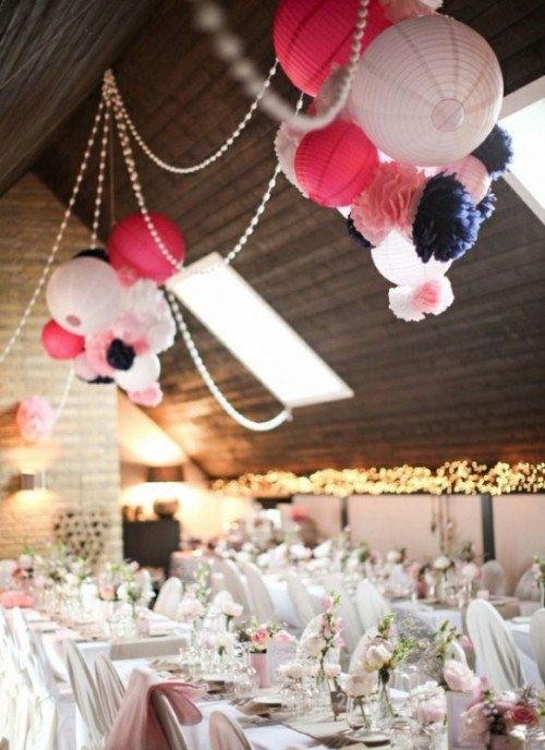 Pour habiller votre plafond, vous pouvez créer des décorations suspendues douces et aériennes en mixant des pompons en papier de soie avec quelques lampions. Ajouter des guirlandes lumineuses peut être une belle idée pour une ambiance plus intimiste.